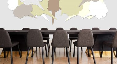 Speech bubbles graphics are positioned above an empty set of tables and chairs
