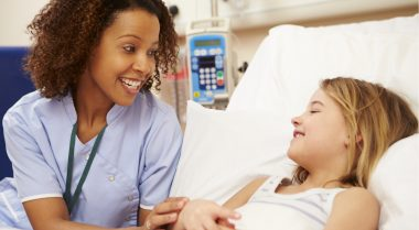 Nurse with young child patient in hospital