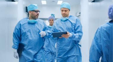 Doctors consult tablet on the way back from surgery